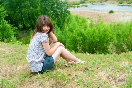 the girl sits on the rock over the river Stock Photo - 17755822