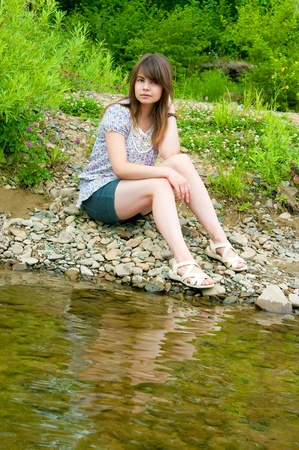 The sexual brunette sits on  river bank Stock Photo - 17847419