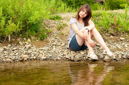 The sexual brunette sits on  river bank Stock Photo - 17847422