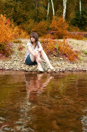 The sexual brunette sits on  river bank Stock Photo - 17847423