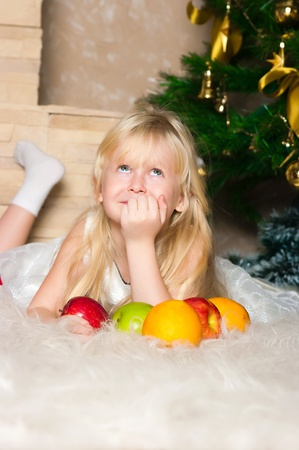 The girl under the Christmas fir-tree with fruit  photo