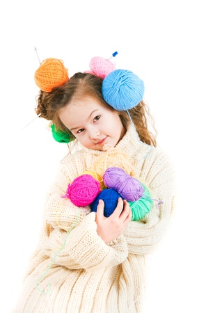 spokes:  The image of the girl with knitting spokes and balls of threads in hair