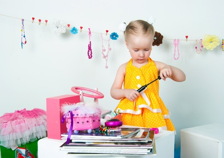 The image of the elegant girl playing with cosmetics and jewelry photo