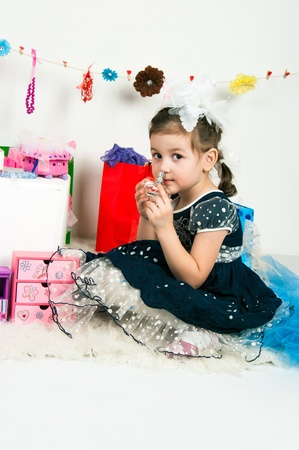 elegant girl playing with cosmetics and jewelry photo