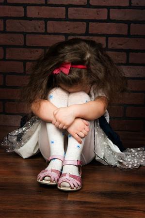 the elegant girl with wavy hair feel sad against a brick wall photo