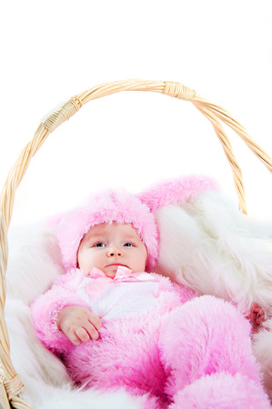 baby in suit: funny newborn baby dressed in Easter bunny  suit  lying in a basket