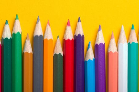 thick colored pencils against a yellow background color photo