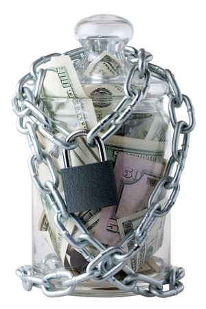 pricey: Locked glass jar full of the American banknotes.  Stock Photo