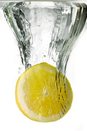 Lemon in the flight surrounded and followed by water bubbles photo