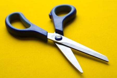 open shears on blue background. Small DOF photo