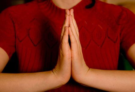 worshipers: young womens hands  clasped in prayer. Small DOF. Stock Photo