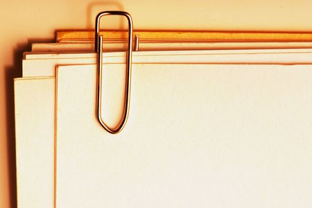 view of a paper clip with stack of blank paper  photo