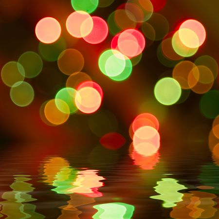 Brightly colored lights reflected in water . Forced out of focus.  photo