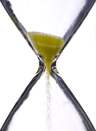 Close view of sand flowing through an hourglass. photo