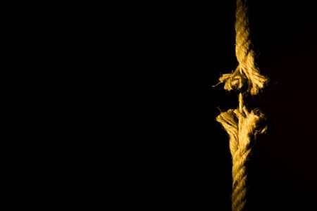 frayed: Frayed rope breaking on a dark background Stock Photo