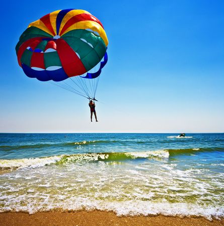 parasailing: One man is parasailing over the blue sea. Stock Photo