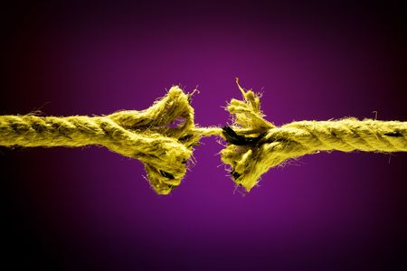 powerless: Frayed rope breaking on a dark background Stock Photo