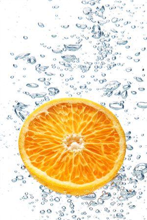 dropped: Un fondo de la formaci�n de burbujas en el agua azul despu�s de naranja se ha ca�do en ella. Foto de archivo