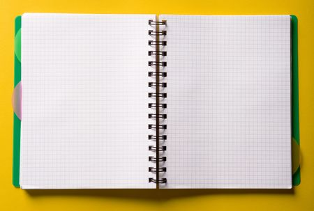 Open spiral notebook on yellow table Stock Photo