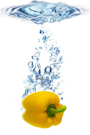 yellow pepper are dropped into water photo
