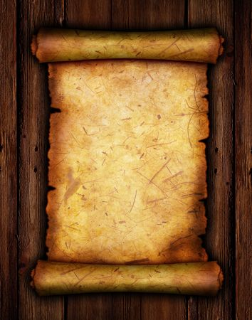 torn edges: An ancient paper with torn edges, on a brown wooden surface. Stock Photo