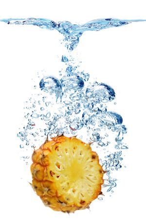 Bubbles forming in blue water after pineapple is dropped into it.