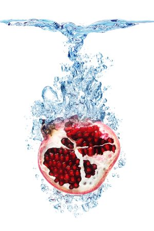 pomegranates: Pomegranate splashing into water against a white background.