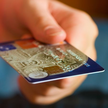 charge card: Hand holding credit cards. Small DOF.