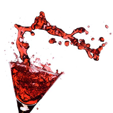 Red Martini being poured in a martini glass; isolated on a white background.