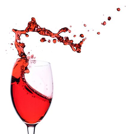 Red Wine being poured in a wine glass; isolated on a white background.