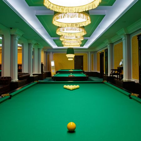 Yellow sphere on a billiard table in a night club Stock Photo