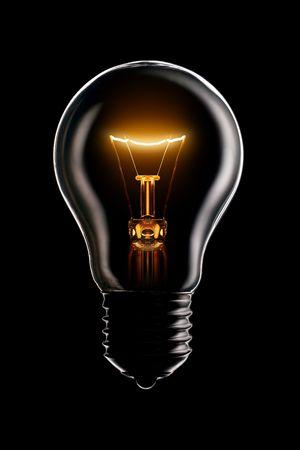 yellow lamp: Glowing lamp on black background Stock Photo