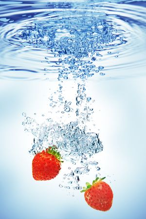 strawberry splash: A background of bubbles forming in water after strawberries are dropped into it. Stock Photo