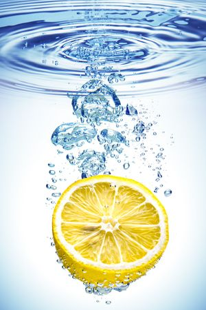 with lemon: A background of bubbles forming in blue water after lemon is dropped into it. Stock Photo