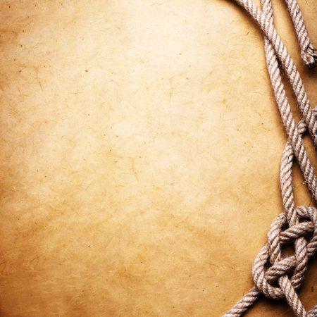 knotting: Una vecchia corda legata in un nodo di et� su carta marrone. Camera per il testo a disposizione.