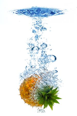 Bubbles forming in blue water after pineapple is dropped into it. photo
