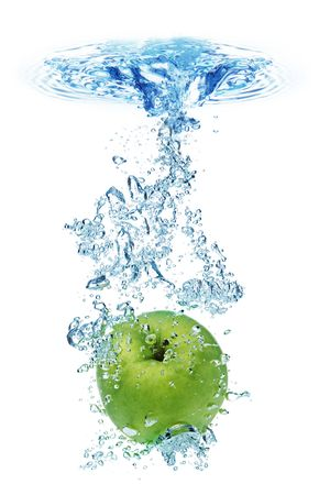 Green apple under water with a trail of transparent bubbles. photo
