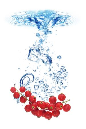 Bubbles forming in blue water after red currant is dropped into it. photo