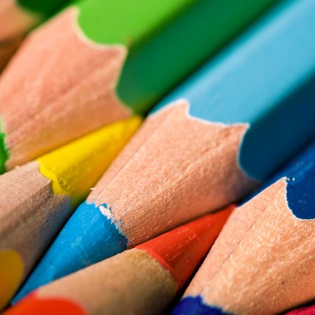 Thick pencils are arranged in a background photo