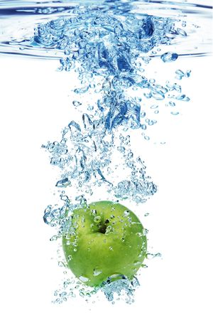 Green apple under water with a trail of transparent bubbles. Stock Photo