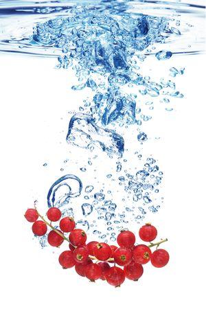 fr�chte in wasser: Blasen bilden im blauen Wasser, nachdem eine Rote Johannisbeere hinein gel�scht wurde.