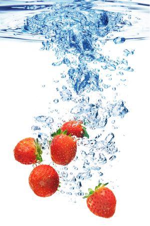 dropped: Un fondo de la formaci�n de burbujas en el agua despu�s de las fresas se dej� caer en ella. Foto de archivo