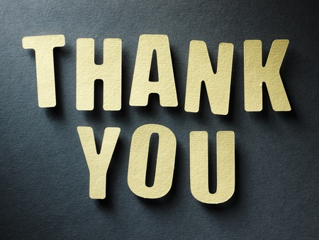 The word Thank you in cut out paper letters on paper background photo