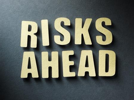risks ahead: La palabra Riesgos adelante en cortar las cartas de papel en el fondo de papel