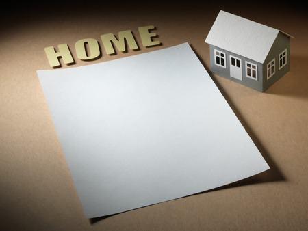 paper house, sheet and the word home on the cardboard surface photo
