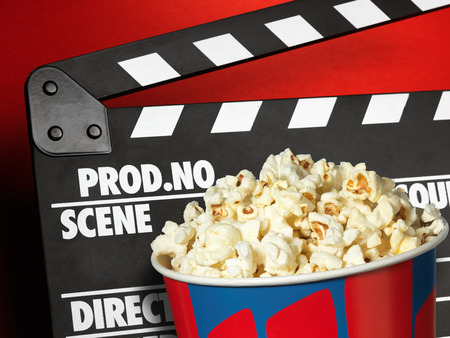 Clapper board and popcorn box on red background photo