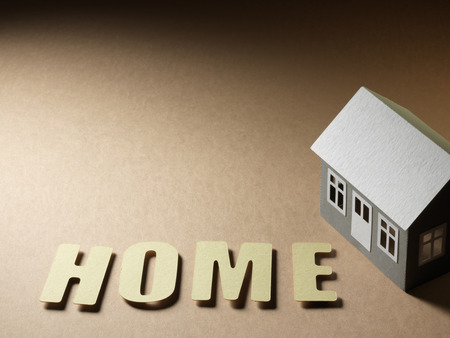 paper house and the word home on the cardboard surface photo