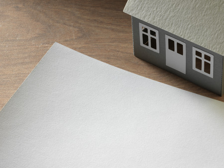 paper house and sheet of paper on the table photo