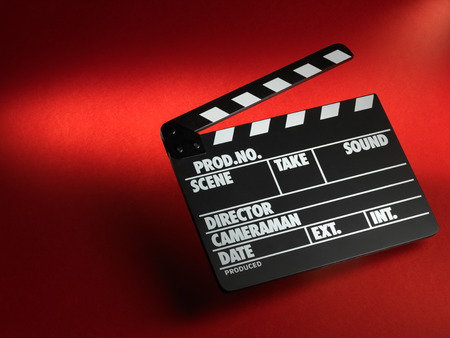 film director: Clapper board on red background Stock Photo