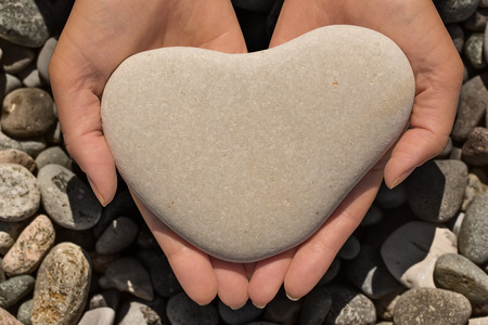 heart of stone: Female hands holding a natural heart-shaped stone in cupped palms over a background of water worn pebbles